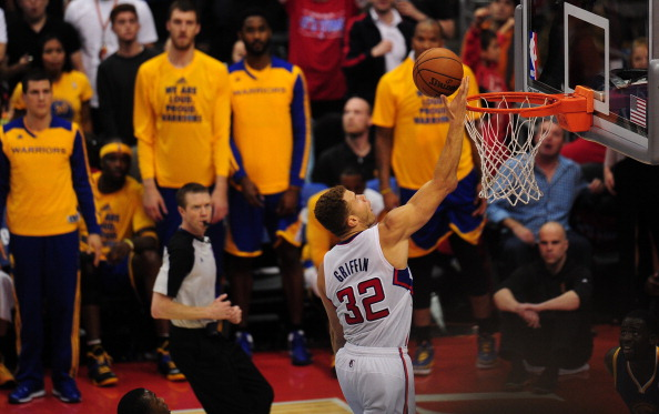 Players on the bench for the Golden State Warriors can only watch as Blake Griffin of the Los Angeles Clippers scores uncontested late in game 7 of their NBA first round series on May 3, 2014 in Los Angeles, California, where the LA Clippers defeated the GS Warriors 126-121.