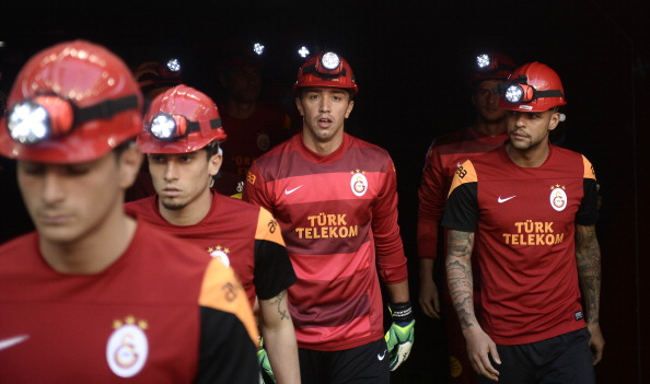Galatasaray players with their helmets to commemorate the ones who lost their lives following the coal mine fire in Soma, Manisa on May 13, 2014, prior to the match with Kayseri Erciyesspor at Ali Sami Yen Sports Complex on May 17, 2014.