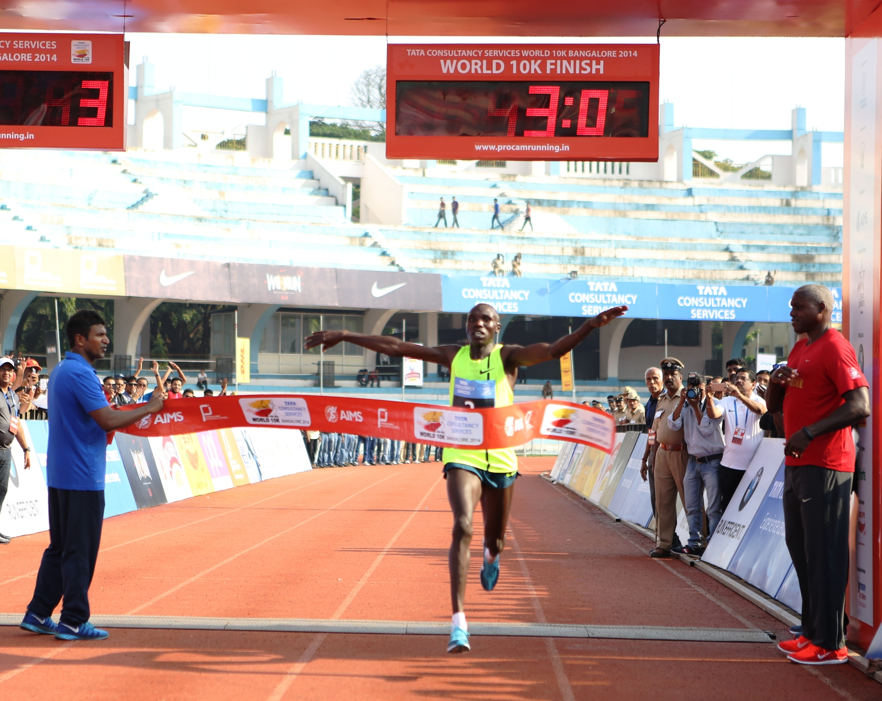 Kenya's Geoffrey Kamworor-Kipsang crosses the finish line in 00:27:44 seconds with New Course record to win the overall men's title at the TCS World 10K Bangalore 2014. In the picture also seen is Carl Lewis, Event Ambassador & Puneeth Rajkumar, Face of the Event.