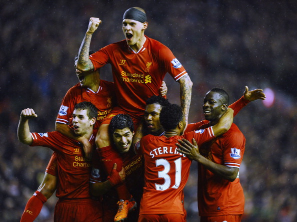 Martin Skrtel of Liverpool jumps on the shoulders of Daniel Sturridge (2nd R) after the third goal during during the Barclays Premier League match between Liverpool and Everton at Anfield on January 28, 2014 in Liverpool, England.