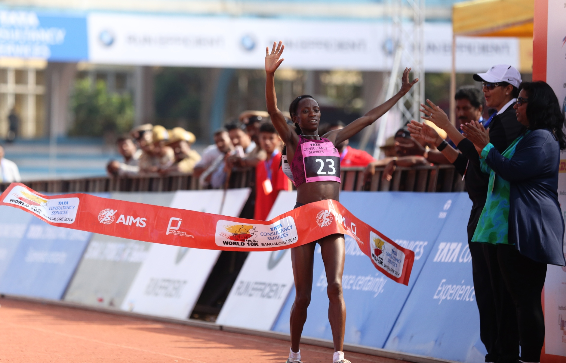 Kenya's Lucy Kabuu crosses the finish line in 00:31:48 seconds with New Course record to win the overall women's title at the TCS World 10K Bangalore 2014. In the picture also seen are Anju Bobby George (Olympian) and Dr. N. Nagambika Devi, IAS, Principal Secretary to the Government, Youth Empowerment and Sports Department.
