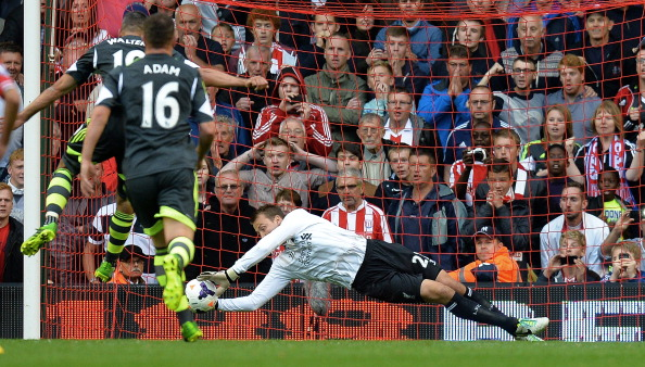 Simon Mignolet (R) saves a penalty from Stoke City's Irish forward Jon Walters (L) during the season's opening Premier League football match between Liverpool and Stoke City at Anfield