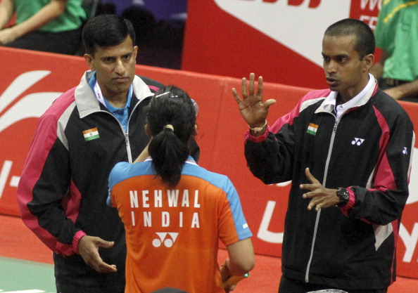 Indian badminton player Saina Nehwal having discussion with coach Pullela Gopichand (R) during a match against Indonesia badminton player Lindaweni Fanetri at the Uber Cup 2014