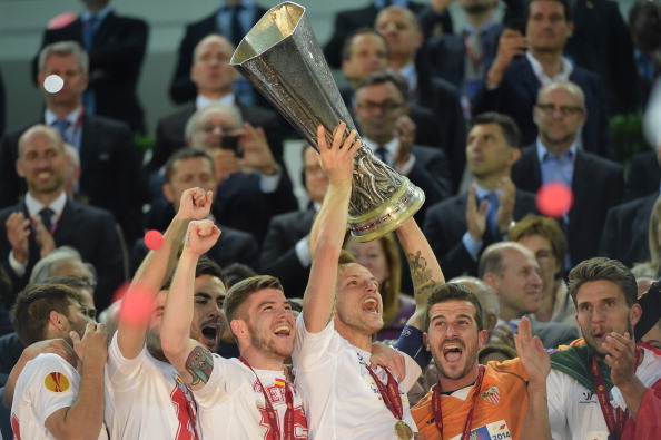 Sevilla players celebrate with the trophy
