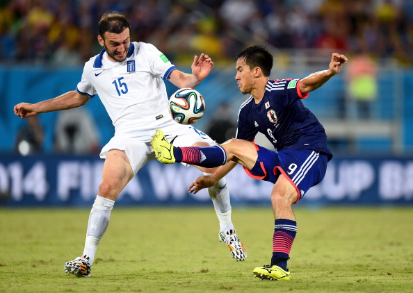 Shinji Okazaki of Japan and Vasilis Torosidis of Greece compete for the ball during the 2014 FIFA World Cup Brazil Group C match between Japan and Greece at Estadio das Dunas on June 19, 2014 in Natal, Brazil