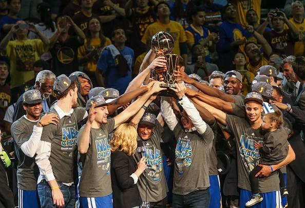 deb7ecafcdd Golden State Warriors hold the Larry O Brien trophy aloft on Tuesday night
