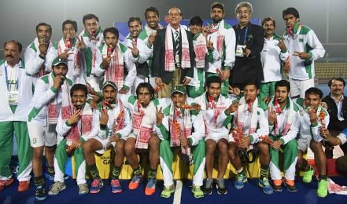 The Pakistan players pose after winning hockey gold