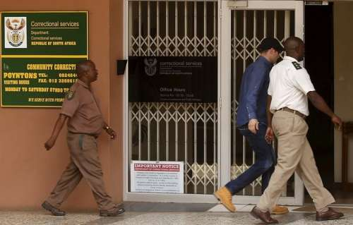 Oscar Pistorius (2nd R) is escorted by correctional services officials as he arrives to get an electronic tag after he was granted bail in Pretoria, South Africa December 8, 2015. REUTERS/Siphiwe Sibeko/Files