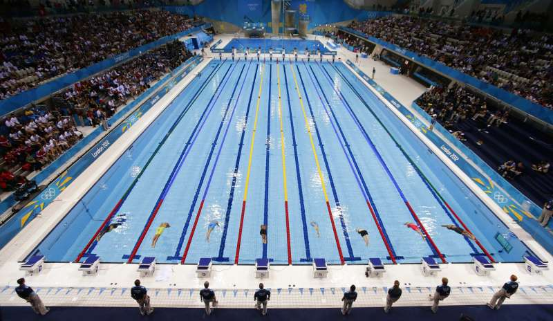 swimmers dive into the water to start heat 5 of the womens 50m freestyle event during