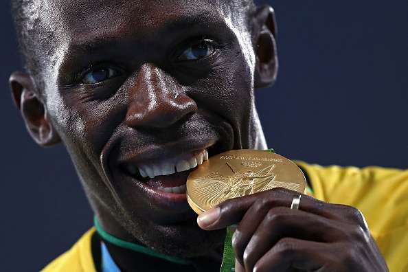 RIO DE JANEIRO, BRAZIL - AUGUST 20:  Gold medalist Usain Bolt of Jamaica bites his gold medal during the medal ceremony for the Men