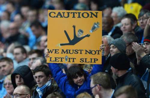 MANCHESTER, ENGLAND - MAY 07: A Manchester City fan holds a message for his team referencing Steven Gerrard's slip against Chelsea during the Barclays Premier League match between Manchester City and Aston Villa at Etihad Stadium on May 7, 2014 in Manchester, England.  (Photo by Michael Regan/Getty Images)