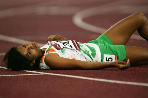 DOHA, QATAR - DECEMBER 11:  P. Jaisha Orchatteri of India #2098 lays on the track after finishing third for the bronze medal in the Women's 5000m during the 15th Asian Games Doha 2006 at the Khalifa Stadium December 11, 2006 in Doha, Qatar.   (Photo by Clive Rose/Getty Images for DAGOC)