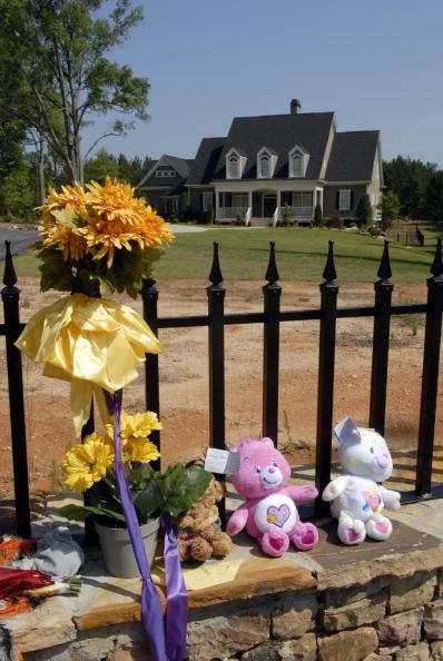 FAYETTEVILLE, GA - JULY 1: A make-shift shrine adorns the fence of the home of pro wrestler Chris Benoit July 1, 2007 in Fayetteville, Georgia. Police say Benoit killed his wife and seven year-old son, before hanging himself June 24 in the house. (Photo by Barry Williams/Getty Images)
