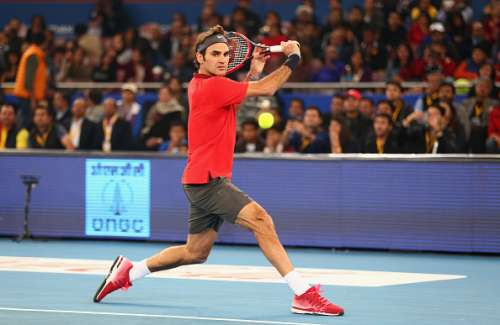 DELHI, INDIA - DECEMBER 08:  Roger Federer of the Indian Aces plays a backhand against Novak Djokovic of the UAE Royals during the Coca-Cola International Premier Tennis League third leg at the Indira Gandhi Indoor Stadium December 8, 2014 in Delhi, Delhi.  (Photo by Clive Brunskill/Getty Images for IPTL 2014)