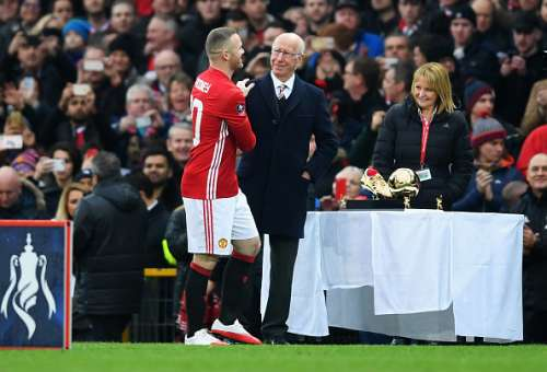 MANCHESTER, ENGLAND - JANUARY 29:  Wayne Rooney of Manchester United is presented with an award for becoming the club's top goal scorer of all time from  Sir Bobby Charlton prior to the Emirates FA Cup Fourth round match between Manchester United and Wigan Athletic at Old Trafford on January 29, 2017 in Manchester, England. Rooney's total of 250 goals for Manchester United in all competitions surpasses the record previously held by Sir Bobby Charlton.  (Photo by Laurence Griffiths/Getty Images)