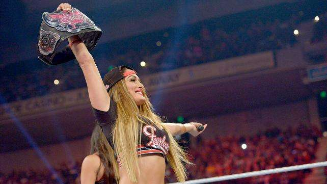 Nikki Bella in the ring holding up the Divas Championship