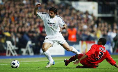 MADRID, SPAIN - MARCH 24:  Luis Figo of Real Madrid is tackled by Patrice Evra of Monaco during the UEFA Champions League Quarter Final match between Real Madrid and Monaco at The Bernabeu on March 24, 2004 in Madrid, Spain.  (Photo by Clive Mason/Getty Images)