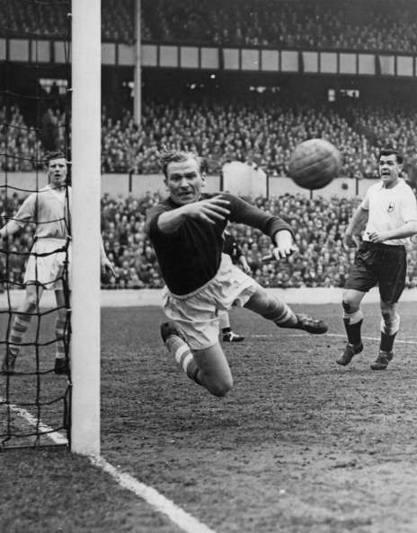German goalkeeper Bert Trautmann (1923 - 2013), of Manchester City FC, makes a save during a First Division match against Tottenham Hotspur at White Hart Lane, London, 24th March 1956. Spurs won the match 2-1. On the right is Spurs centre-forward Len Duquemin (1924 - 2003). (Photo by Ron Burton/Keystone/Hulton Archive/Getty Images)
