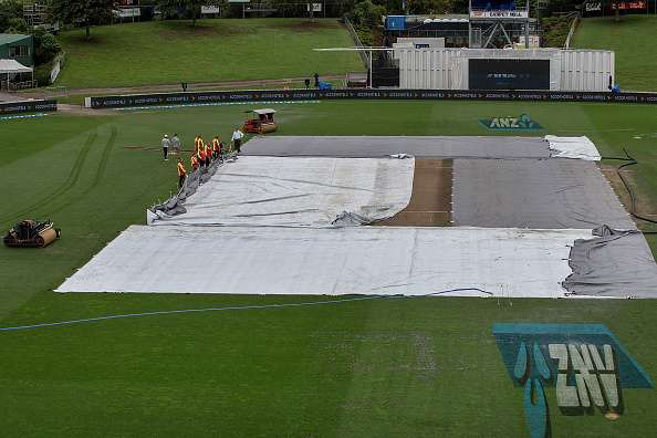 HAMILTON, NEW ZEALAND - MARCH 29:  Ground staff supervised by reserve umpire Chris Brown (top) adjust the covers as rain delays the start of day five of the Test match between New Zealand and South Africa at Seddon Park on March 29, 2017 in Hamilton, New Zealand.  (Photo by Dave Rowland/Getty Images)