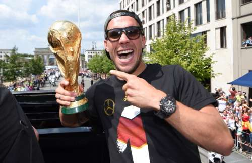 BERLIN, GERMANY - JULY 15:  Lukas Podolski celebrates on the open top bus at the German team victory ceremony on July 15, 2014 in Berlin, Germany. Germany won the 2014 FIFA World Cup Brazil match against Argentina in Rio de Janeiro on July 13.  (Photo by Markus Gilliar - Pool/Getty Images)