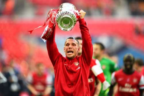 LONDON, ENGLAND - MAY 17:  Lukas Podolski of Arsenal celebrates victory with the trophy after the FA Cup with Budweiser Final match between Arsenal and Hull City at Wembley Stadium on May 17, 2014 in London, England.  (Photo by Shaun Botterill/Getty Images)