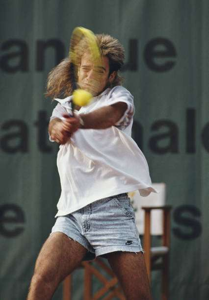 Andre Agassi of the United States wearing his jean style shorts makes a double hand return during a Men