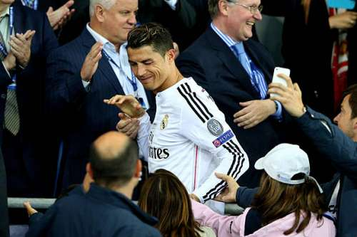 CARDIFF, WALES - AUGUST 12:  Cristiano Ronaldo of Real Madrid winks at fans as he goes up to receive his winners medal following his team's 2-0 victory during the UEFA Super Cup between Real Madrid and Sevilla FC at Cardiff City Stadium on August 12, 2014 in Cardiff, Wales.  (Photo by Clive Mason/Getty Images)