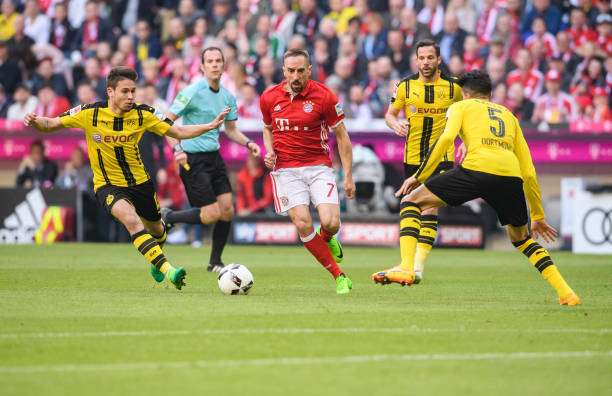 MUNICH, GERMANY - APRIL 08: Franck Ribery of Bayern Muenchen in action against Raphael Guerreiro of Dortmund (L) and Marc Aregall Bartra of Dortmund (R) during the Bundesliga match between Bayern Muenchen and Borussia Dortmund at Allianz Arena on April 8, 2017 in Munich, Germany. (Photo by Alexander Scheuber/Getty Images Fuer MAN)