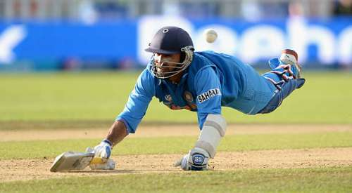 BIRMINGHAM, ENGLAND - JUNE 15:  Dinesh Karthik of India dives into his crease during the ICC Champions Trophy match between India and Pakiatan at Edgbaston on June 15, 2013 in Birmingham, England.  (Photo by Gareth Copley/Getty Images)