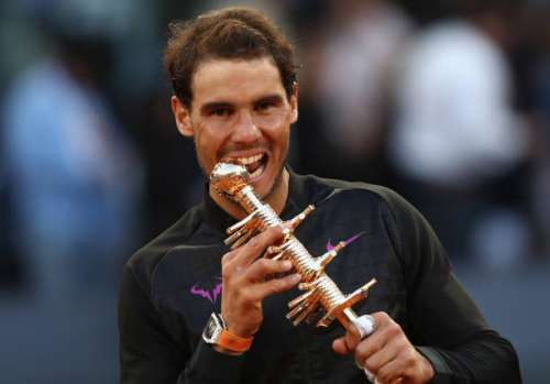 MADRID, SPAIN - MAY 14:  Rafael Nadal of Spain bites the winners trophy after his win over Dominic Thiem of Austria in the final during day nine of the Mutua Madrid Open tennis at La Caja Magica on May 14, 2017 in Madrid, Spain.  (Photo by Julian Finney/Getty Images)