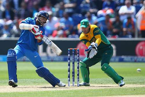 CARDIFF, WALES - JUNE 06:  Shikhar Dhawan (L) of India guides the ball to the offside as AB de Villiers (R) the wicketkeeper of South Africa looks on during the Group B ICC Champions Trophy match between India and South Africa at the SWALEC Stadium on June 6, 2013 in Cardiff, Wales.  (Photo by Michael Steele/Getty Images)