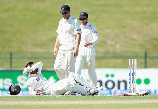 ABU DHABI, UNITED ARAB EMIRATES - NOVEMBER 10:  Ahmed Shehzad of Pakistan lies injured after receiving a bouncer to the head and hitting his wicket , bowled by Corey Anderson of New Zealand during day two of the first test between Pakistan and New Zealand at Sheikh Zayed stadium on November 10, 2014 in Abu Dhabi, United Arab Emirates.  (Photo by Warren Little/Getty Images)