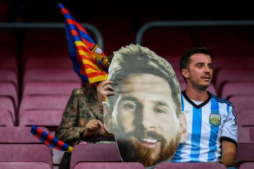 BARCELONA, SPAIN - MAY 21:  A FC Barcelona supporter holds a paper mask of FC Barcelona's Lionel Messi during the La Liga match between Barcelona and Eibar at Camp Nou on 21 May, 2017 in Barcelona, Spain.  (Photo by David Ramos/Getty Images)