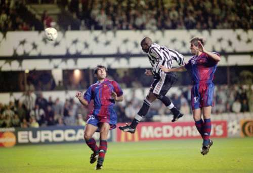 NEWCASTLE UPON TYNE, UNITED KINGDOM - SEPTEMBER 17: Newcastle United striker Faustino Asprilla leaps between Barcelona players Nadal (l) and Sergi Barjuan to head the third Newcastle goal and his hat trick goal during the UEFA Champions League match between Newcastle United and Barcelona at St James' Park on September 17, 1997 in Newcastle Upon Tyne, England.  (Photo by Stu Forster/Allsport/Getty Images)