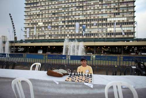 FILE PHOTO: A chess player looks at the board during a game against Israeli grandmaster Alik Gershon at Rabin Square in Tel Aviv, October 21, 2010. REUTERS/Nir Elias/File Photo